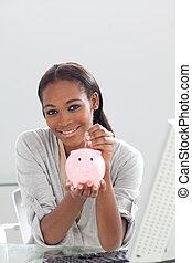 Confident ethnic businesswoman saving money in a piggybank