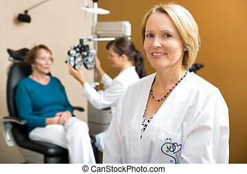 Confident Eye Doctor With Colleague Examining Patient -...