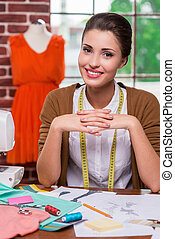 Confident fashion designer. Beautiful young fashion designer holding hands clasped and looking camera while sitting at her working place