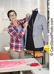 Confident Fashion Designer Pinning Suit On Mannequin - ...
