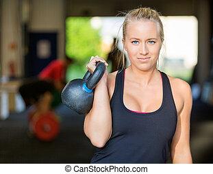 Confident Female Athlete Lifting Kettlebell