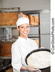 Confident Female Baker Holding Dough Tray At Bakery