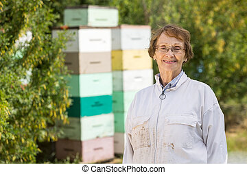 Confident Female Beekeeper At Apiary