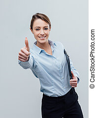 Confident female business executive giving a thumbs up