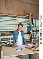 Confident Female Carpenter At Table