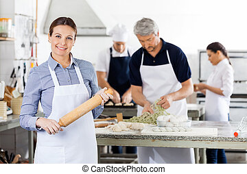 Confident Female Chef Holding Rolling Pin While Colleagues Prepa