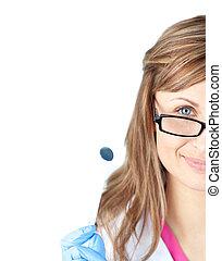 Confident female dental surgeon holding a speculum against...