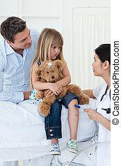 Confident female doctor checking little girl\'s reflex in...