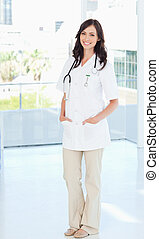 Confident female doctor standing in front of the window while smiling