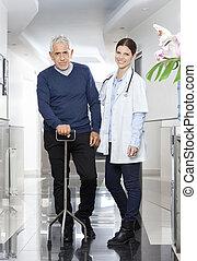 Confident Female Doctor With Senior Man Using Cane
