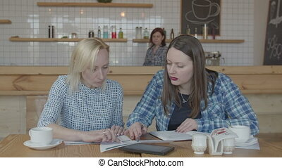 Confident female freelancer working remotely in cafe