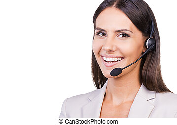 Confident female operator. Beautiful young businesswoman in headset smiling while isolated on white background