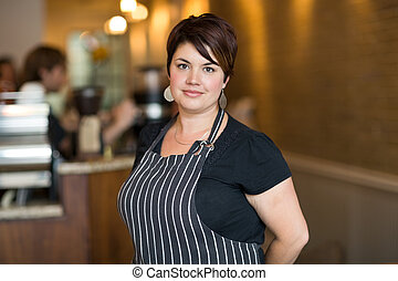 Confident Female Owner Smiling At Cafeteria - Portrait of...