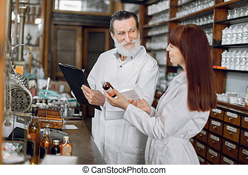 Confident female pharmacist talking with her senior male colleague about side effects of a medicine or pharmaceutical product for sale, working in old ancient pharmacy