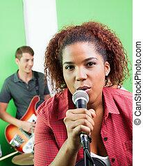 Confident Female Singer Holding Microphone At Recording Studio
