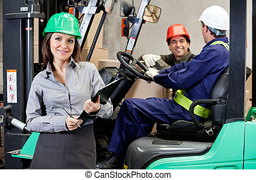 Confident Female Supervisor With Forklift Driver At...