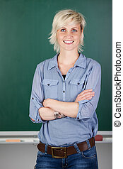 Confident Female Teacher In Front Of Chalkboard