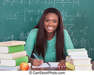 Confident female teacher writing in book at classroom desk -...