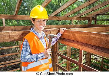 Confident Female Worker Holding Hammer In Timber Frame
