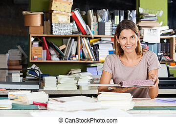 Confident Female Worker Holding Spiral Book In Factory