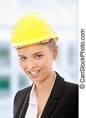 Confident female worker in helmet