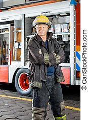 Confident Fireman Standing Against Truck