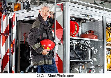 Confident Fireman Standing On Fire Engine