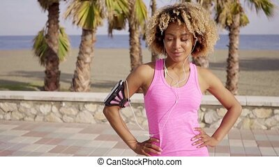Confident fit woman with arm band music player