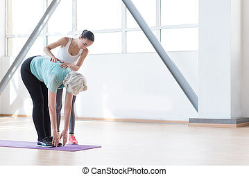 Confident fitness coach standing near the woman