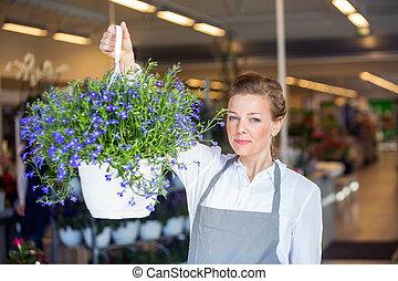 Confident Florist Holding Flower Plant In Shop