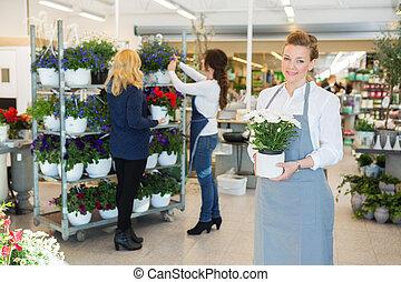 Confident Florist Holding Flower Pot In Shop