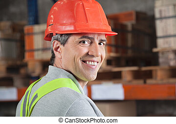 Portrait of confident mid adult foreman at warehouse