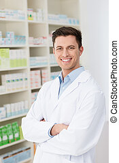 Confident friendly male pharmacist standing with folded arms...