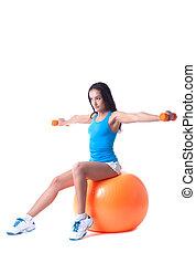 Confident girl exercising with dumbbells in studio