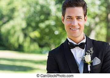 Confident groom in garden