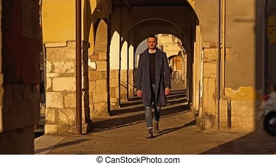 Confident guy in dark coat walks through arch passage with shadow and sunny parts on city embankment along channel in Little Venice at sunset