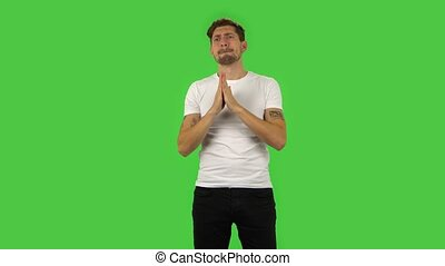 Confident guy is looking with excitement the game with comment. Bearded brown-haired man with light eyes and tattoos in a white T-shirt and black jeans on green screen at the studio