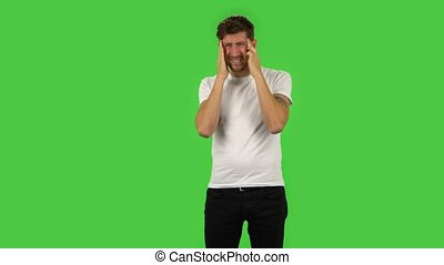 Confident guy is suffering from headache from fatigue. Green screen