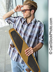 Confident guy resting with skate
