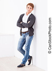 Confident handsome. Full length of handsome young man keeping arms crossed and looking at camera while leaning at the wall