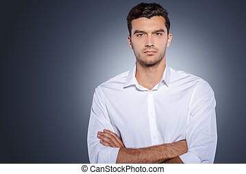 Confident handsome. Handsome young man in white shirt looking at camera and keeping arms crossed while standing against grey background