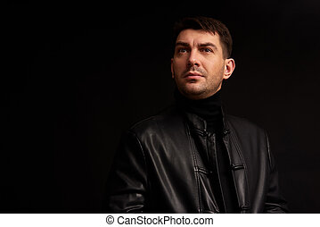 confident handsome man looking away. Black background