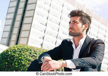 Confident handsome man sitting outdoor. Modern building behind.