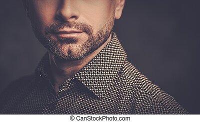 Confident handsome man with beard posing on dark background....