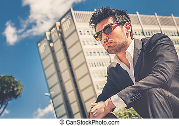 Confident handsome man with sunglasses sitting outdoor. Building behind.