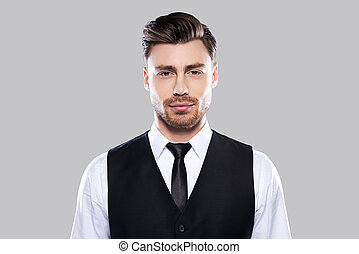 Confident handsome. Portrait of handsome young man in formalwear looking at camera while standing against grey background