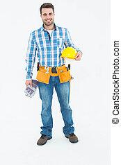 Confident handyman holding hard hat and gloves - Full length...
