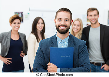 Confident happy businessman clutching a file containing his...