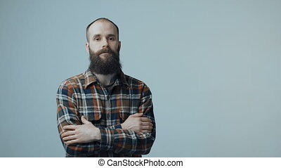 Confident hipster bearded man standing with folded hands