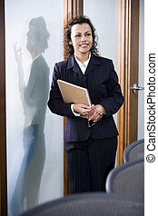 Confident Hispanic businesswoman standing in boardroom, colleague standing outside